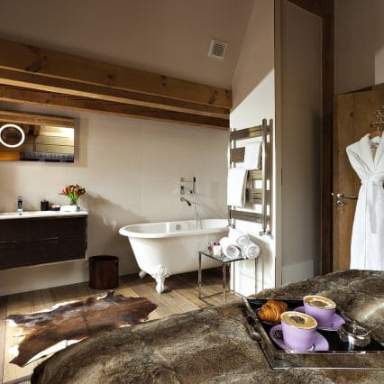 Luxury bedroom in a ski chalet, bath in the room, cosy dressing gown, breakfast in bed turndown service