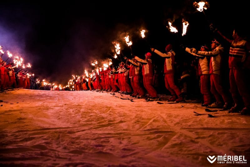 skiers holding torchlights